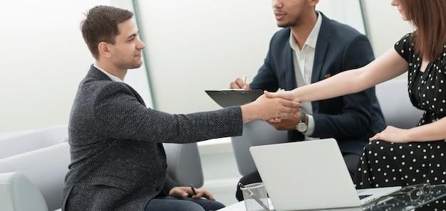 Aperto de mão confiante de parceiros de negócios em uma reunião de negócios