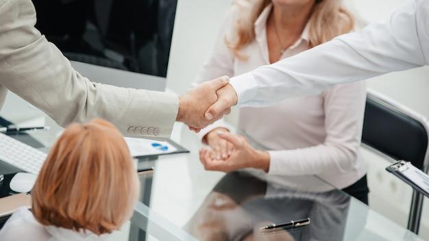 Aperto de mão de colegas em reunião de trabalho