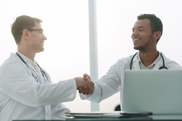 Aperto de mão de colegas médicos sentados na mesa. o conceito de saúde
