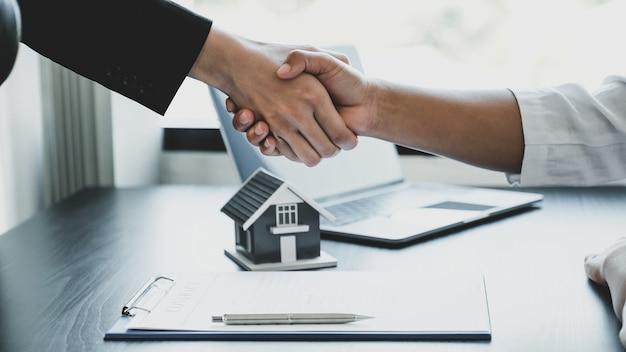 Aperto de mão de corretores e compradores imobiliários após a assinatura de um contrato comercial.