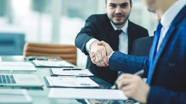 Aperto de mão de dois advogados após discutir os termos de um contrato financeiro em uma mesa no escritório