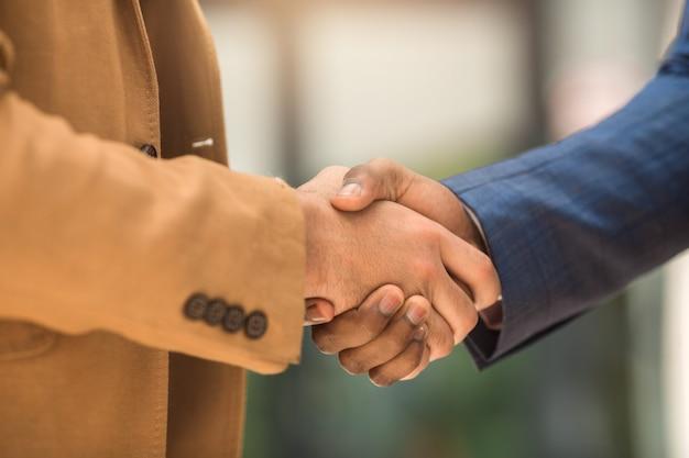 Aperto de mão de dois empresários de terno