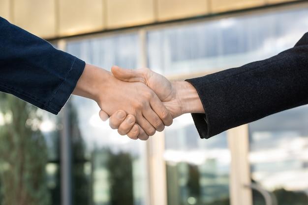 Aperto de mão de dois parceiros de negócios contemporâneos de sucesso contra o exterior de um edifício moderno após negociação e fechamento de acordo