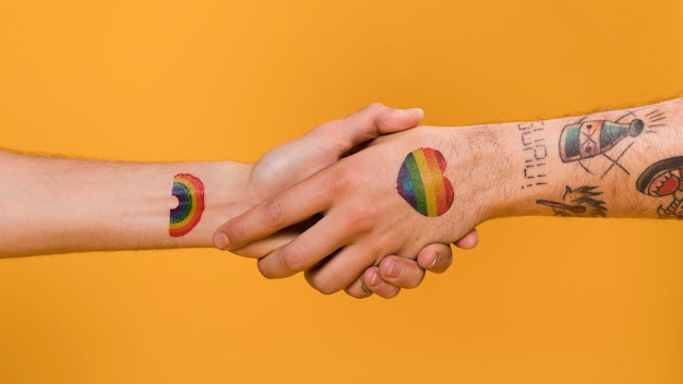 Aperto de mão de duas mãos de homem com orgulho gay padrão multicolorido