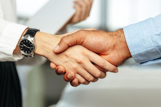 Aperto de mão de empresários femininos e masculinos perto