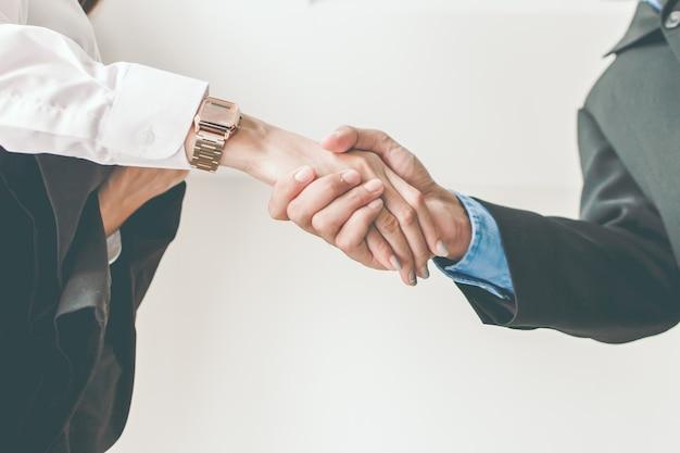 Aperto de mão de empresários masculinos e femininos.