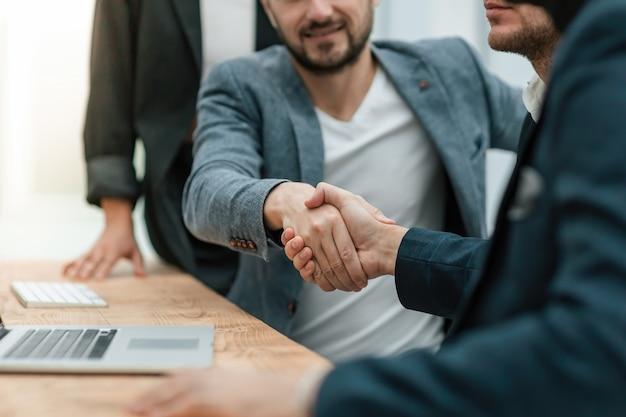 Aperto de mão de empresários sentados à mesa do escritório