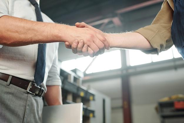 Aperto de mão de jovens parceiros de negócios contemporâneos ou do mestre e seu estagiário dentro da planta industrial