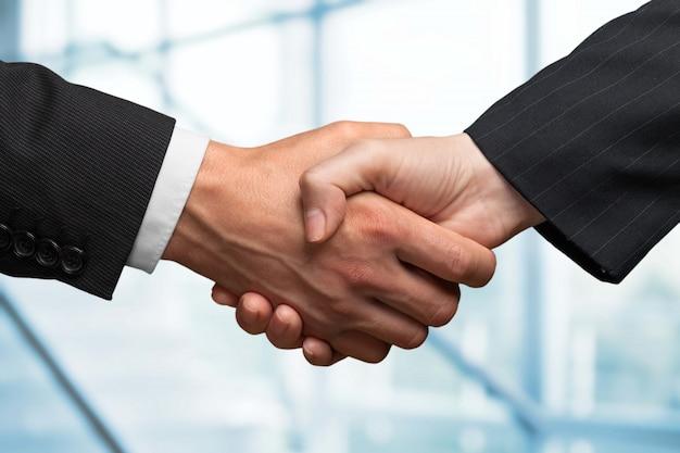 Aperto de mão de negócios e executivos em segundo plano