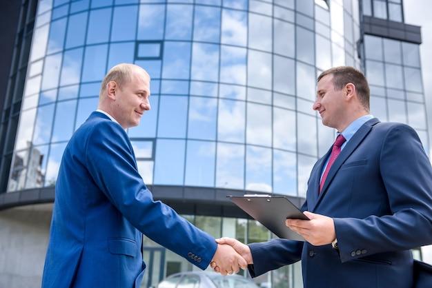 Aperto de mão de parceiros de negócios antes de um grande prédio ao ar livre
