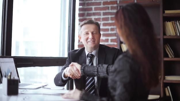 Aperto de mão de parceiros de negócios, sentado em sua mesa no escritório.
