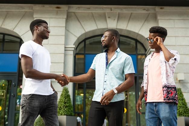 Aperto de mão de três amigos africanos no verão