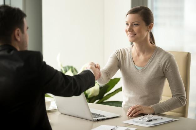 Aperto de mão do empregado do sexo feminino com cliente masculino
