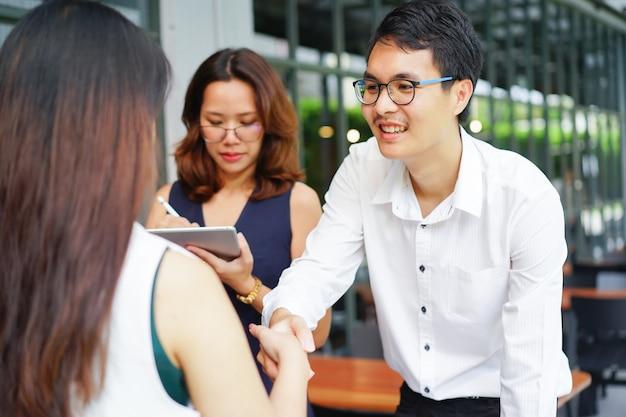 Aperto de mão do empresário com a empresária depois de acordo bem sucedido