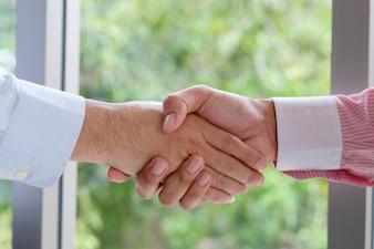 Aperto de mão do empresário no escritório, cooperação empresarial, sucesso no conceito de negócio