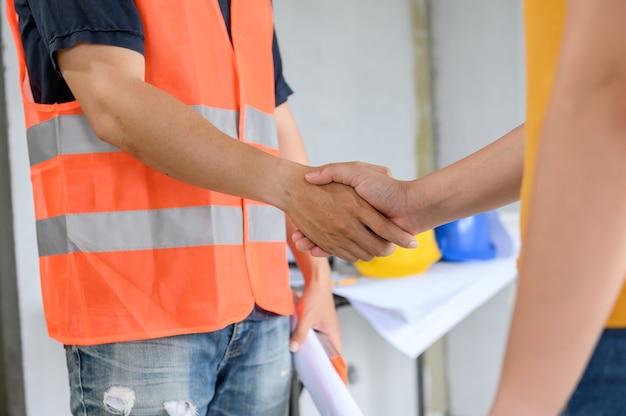 Aperto de mão do engenheiro e arquiteto asiático no canteiro de obras. trabalho em equipe e projeto de construção de conjunto habitacional de sucesso