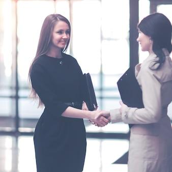 Aperto de mão do gerente da empresa e do cliente no saguão do moderno escritório
