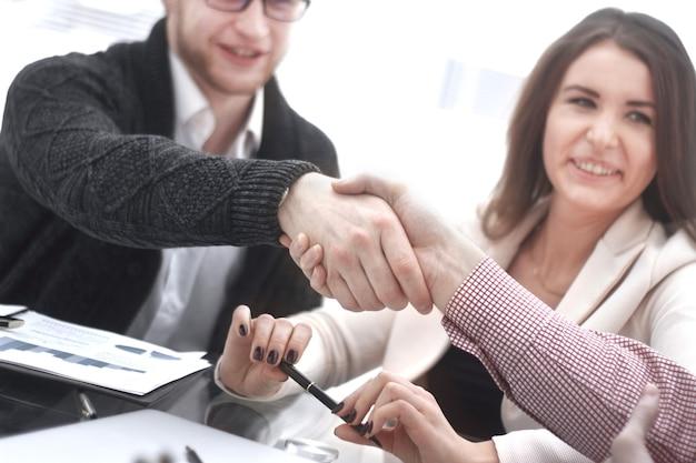 Aperto de mão do gestor e do cliente à mesa do escritório do banco