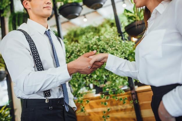 Aperto de mão do jovem empregador bonito com uma mulher atraente. close up, foto recortada.