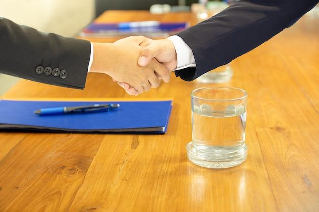 Aperto de mão do negócio na sala de conferências com água e o caderno de vidro na tabela de madeira.