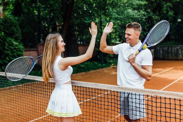 Aperto de mão dos pares na corte de tênis depois de jogar um jogo.