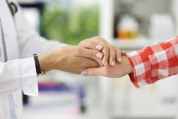 Aperto de mão entre médico e paciente no consultório médico.