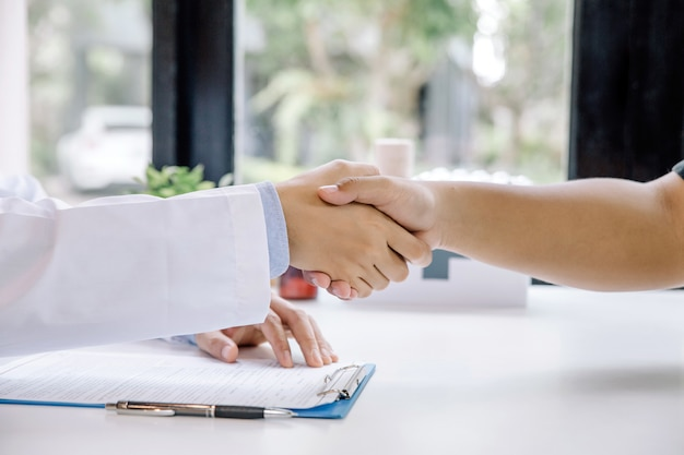 Aperto de mão entre médico e paciente no consultório médico