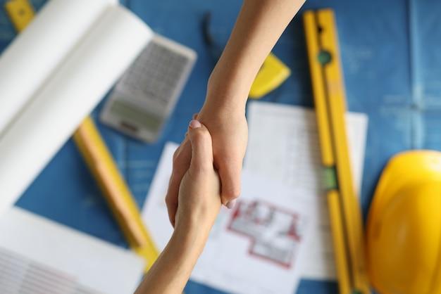 Aperto de mão entre o designer e o cliente sobre os documentos em close-up do estúdio, aprovação bem-sucedida de