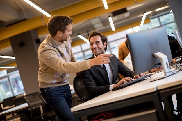 Aperto de mão feliz jovens empresários pela mesa no escritório