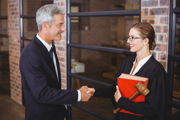 Apertos de mão advogados masculinos e femininos no escritório