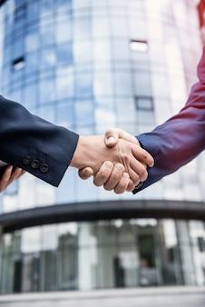 Apertos de mão contra novo centro de negócios close-up