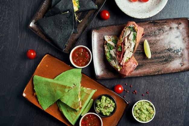 Apetitosa cozinha mexicana em lata na mesa - burritos e quesadillas