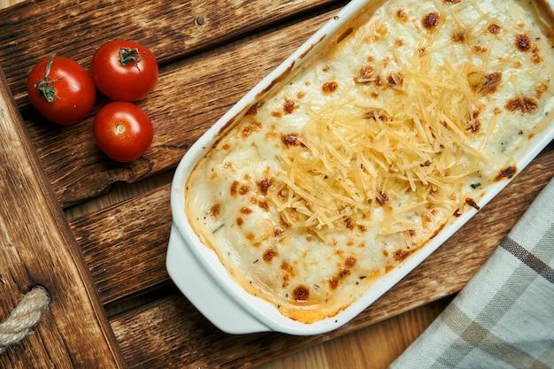 Apetitosa lasanha italiana em uma assadeira especial. lasanha caseira com queijo derretido e vários recheios (legumes, carne) em uma mesa de madeira