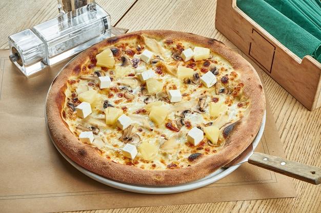 Apetitosa pizza assada com molho branco, frango, abacaxi e cogumelos com uma crosta crocante em uma mesa de madeira. configuração de mesa de restaurante. fechar-se