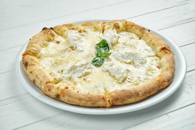 Apetitosa, pizza caseira de 4 queijos com queijo azul, mussarela, parmesão e strachatella em um prato branco sobre um branco