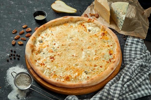 Apetitosa pizza italiana 4 queijos em uma composição com ingredientes em uma mesa preta