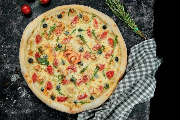 Apetitosa pizza italiana com camarões, mexilhões, azeitonas, tomates e rúcula em uma composição com ingredientes sobre uma mesa preta. vista do topo