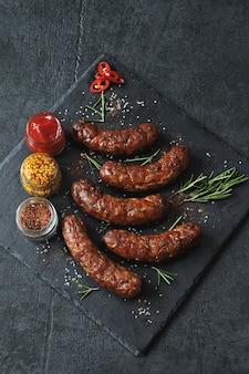 Apetitosas salsichas bávaras ou de munique com temperos e molhos em uma tábua de pedra