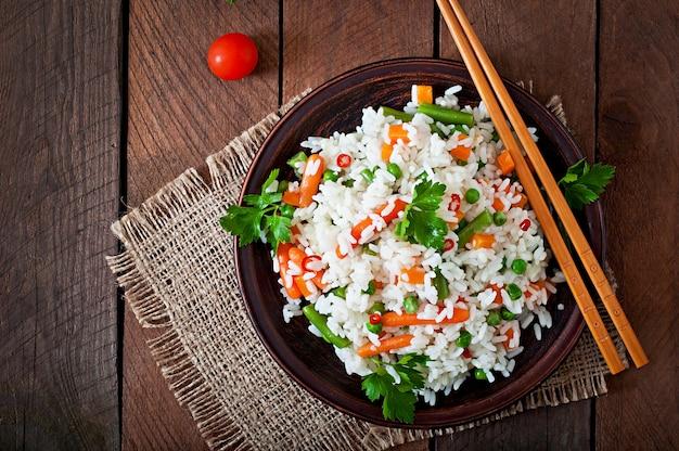 Apetitoso arroz saudável com legumes em chapa branca sobre uma mesa de madeira.
