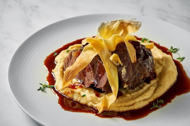 Apetitoso bife de bochecha de búfalo guarnecido com purê de batata e molho vermelho, servido em prato branco sobre mármore