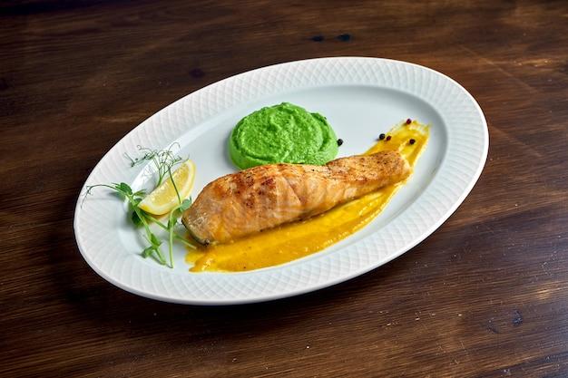 Apetitoso bife de salmão grelhado com molho amarelo e purê de ervilha verde, servido em prato branco sobre superfície de madeira