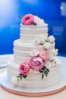 Apetitoso bolo de massa fresca coberto por glacê branco creme e decorar flores doces servindo na mesa