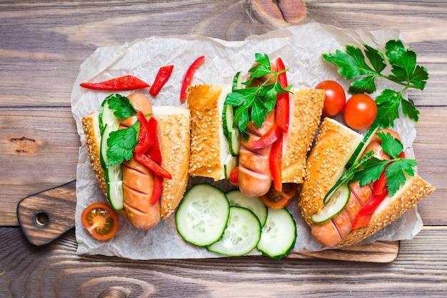 Apetitoso cachorro-quente de salsichas fritas, pão de gergelim e legumes frescos em uma placa de corte sobre uma mesa de madeira
