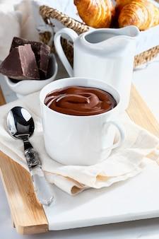 Apetitoso café da manhã com uma deliciosa xícara de chocolate quente espesso e bebível, junto com croissants.