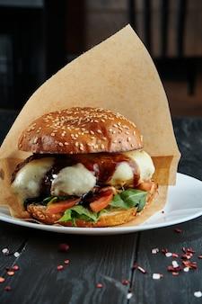 Apetitoso e suculento hambúrguer derretido mussarela, molho balsâmico, carne, tomate e rúcula em um prato branco com batatas fritas. feche acima, vertical