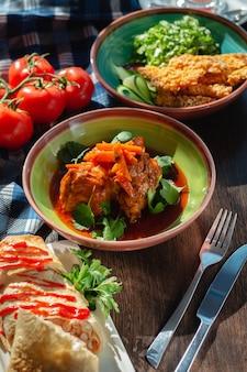 Apetitoso goulash de carne com molho (carnes e vegetais), cenoura e coentro na mesa em lindo ambiente com luz solar