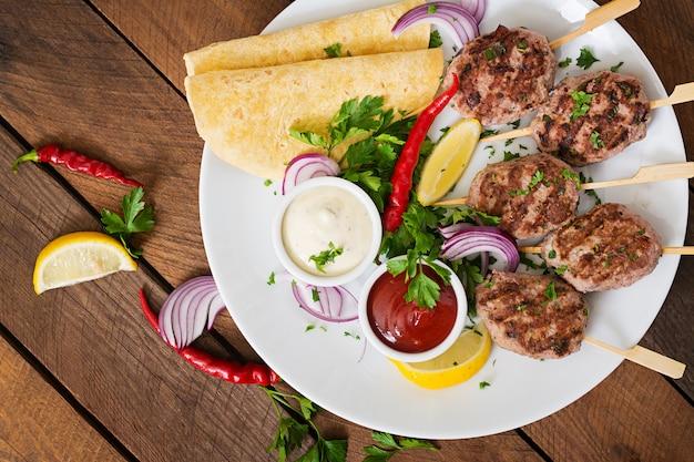 Apetitoso kofta kebab (almôndegas) com tacos de molho e tortilhas num prato branco