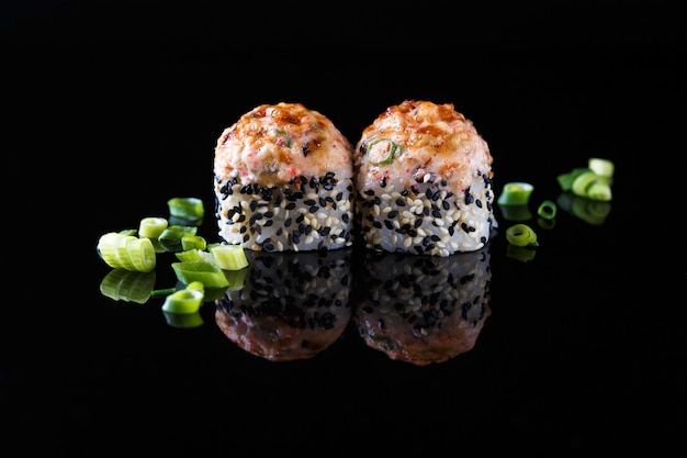 Apetitoso rolo de sushi assado com peixe, cebolinha em um fundo preto com reflexão menu e restaurante