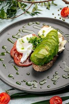 Apetitoso sanduíche de abacate com tomate e ovo escalfado no café da manhã
