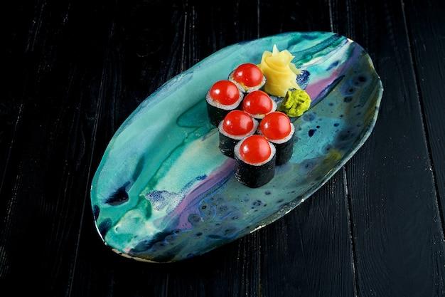 Apetitoso sushi japonês - maki com legumes servido em um prato com gengibre e wasabi em um fundo de madeira preta.